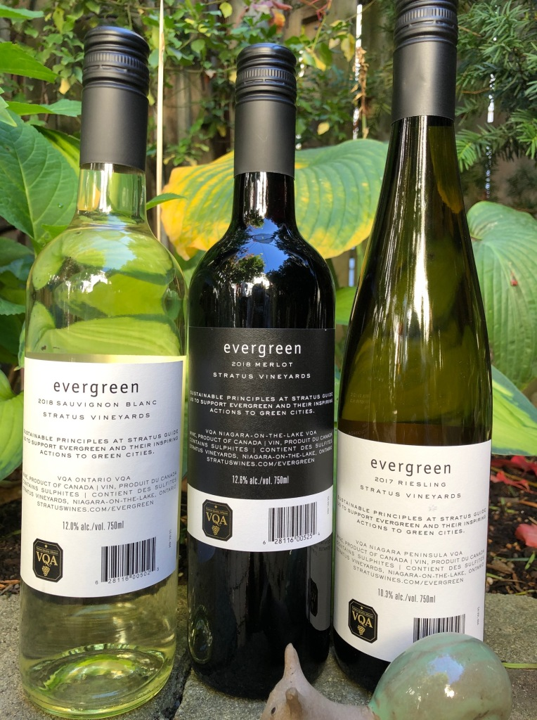Evergreen Sauvignon Blanc and merlot and Riesling bottles with Stratus's sustainability values on back of bottles