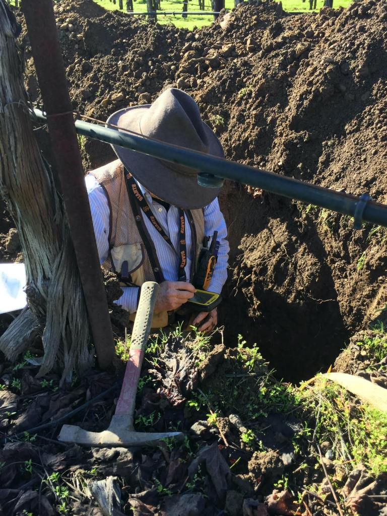 Deep soil pit with man inside measuring content