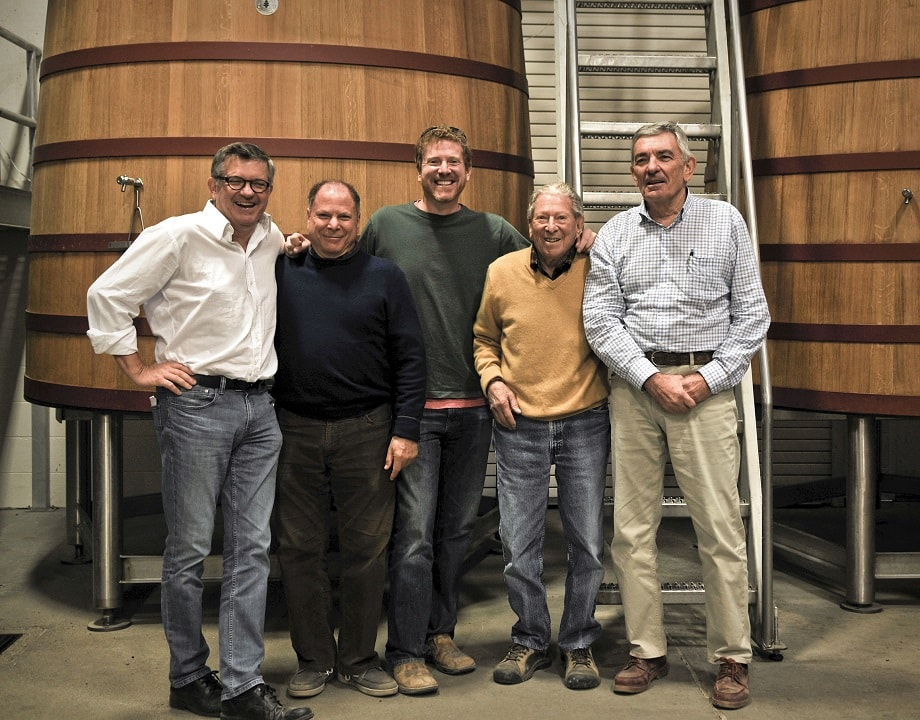 five men in front of large wooden wine tanks