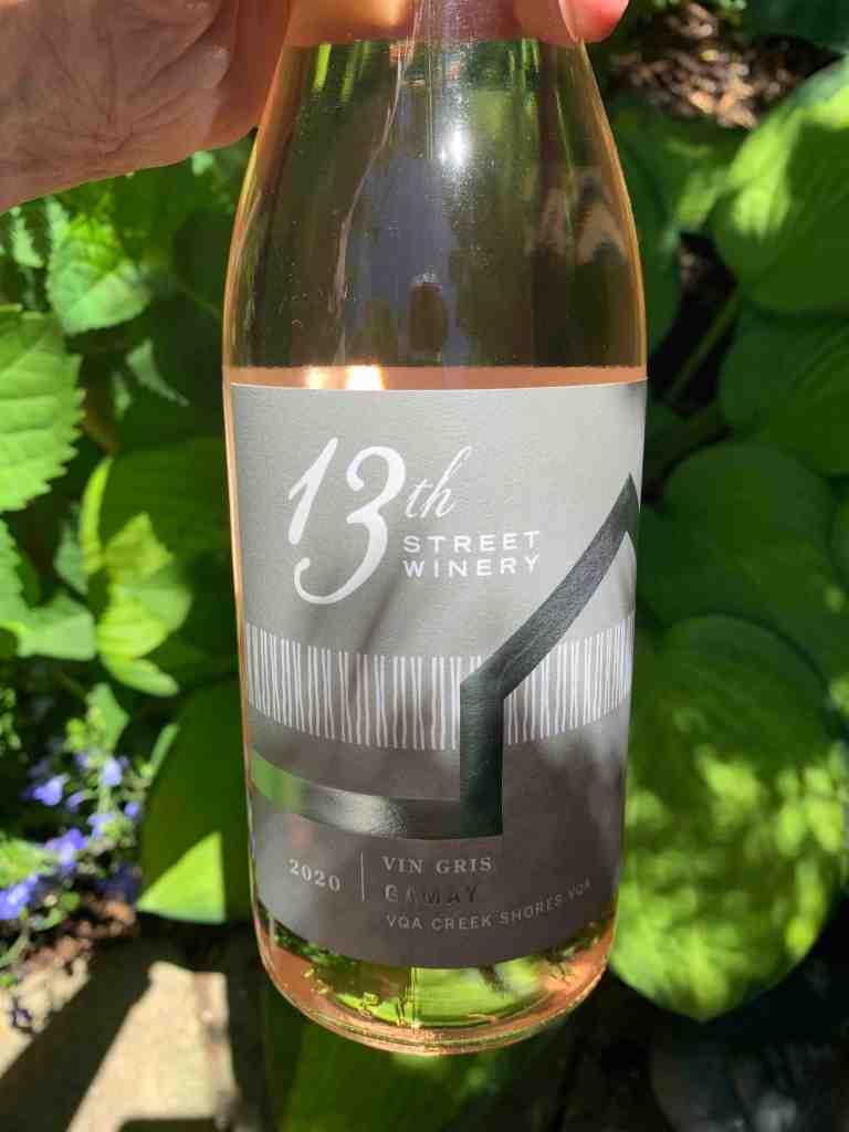 Bottle of 13th Street Gamay wine in garden