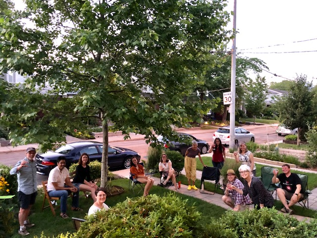 a group of people on front lawn enjoying rose wine